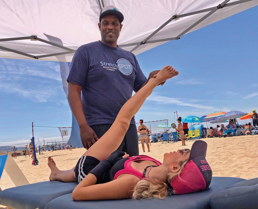 woman being stretched on a table by a therapist on the beach