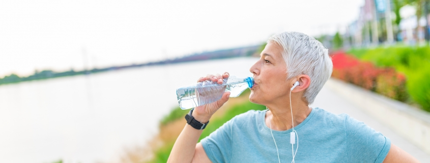 woman in blue top drinking water with headphones in