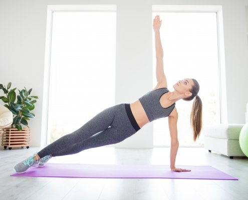 girl doing side plank in a living room