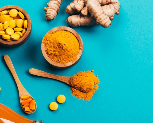 overhead shot of ginger, turmeric and vitamin pills on a blue background