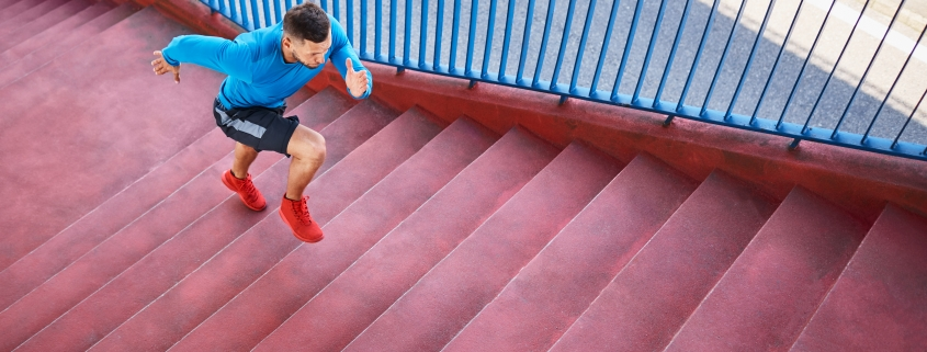 man doing hiit training on red stairs