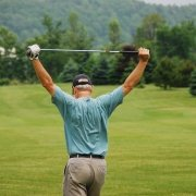 rear view of man holding golf club above his head in stretching motion