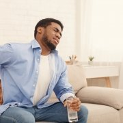 man on sofa holding his back in pain