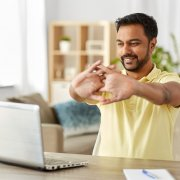 smiling man in front of laptop stretching out his arms