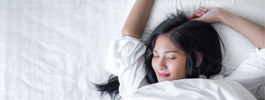 relaxed sleeping woman in white sheets