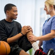 basketball player on a doctor's table looking at a female doctor